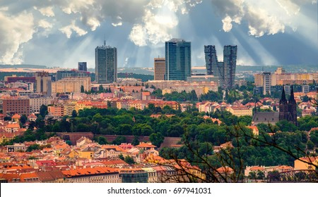 Aerial view of the Old Town in Prague, Czech Republic. Skyscrapers in the background with cloudy blue sky and sun rays.