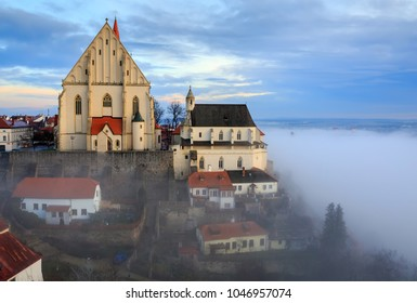 Aerial view of the old town of Znojmo with St. Nicholas Church and St. Wenceslas chapel, built on the steep bank of the Thaya river, shot on a foggy winter day. Znojmo, Czech Republic, Europe.