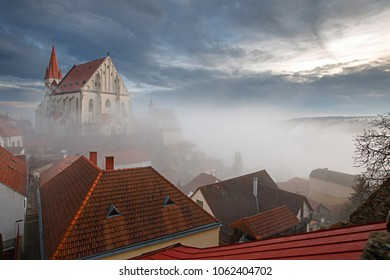 Aerial view of the old town of Znojmo with St. Nicholas Church, built on the steep bank of the Thaya river, shot on a foggy winter day. Znojmo, South Moravia, Czech Republic.