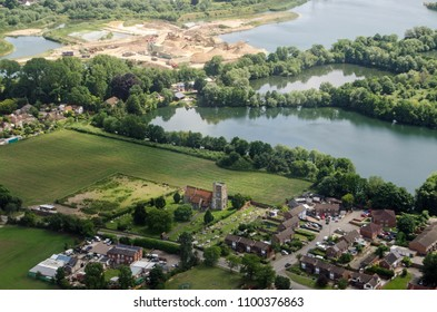 Aerial view on the approach to London's Heathrow Airport of the parish church of St Michael in Horton near Slough in Berkshire.  Beyond the church is the Cemex cement works.