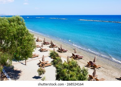 Aerial view on a beach chairs and umbrellas on sand beach. Limassol, Cyprus. Turquoise sea water. Concept for rest, relaxation, holidays, spa, resort.