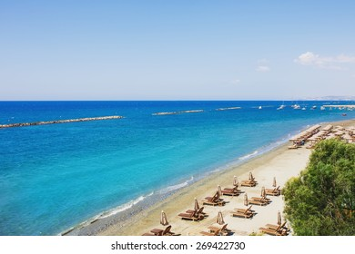 Aerial view on a beach chairs and umbrellas on sand beach. Turquoise sea water. Concept for rest, relaxation, holidays, spa, resort. Limassol, Cyprus.