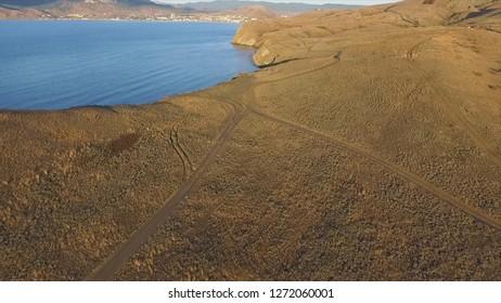 Aerial view on the beach of Sudak in Crimea, Black Sea coast. Shot. The Crimean coast from above. Beautiful Crimean landscape, black sea and mountain views