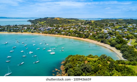 Aerial view on beautiful bay at sunny day with sandy beach and residential suburbs on the background. Waiheke Island, Auckland, New Zealand.