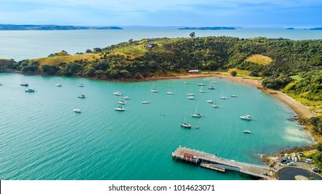Aerial view on beautiful bay at sunny day with sandy beach and residential houses on the background. Waiheke Island, Auckland, New Zealand