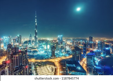 Aerial view on big futuristic city by night. Skyscrapers of Dubai, United Arab Emirates. Nighttime skyline.