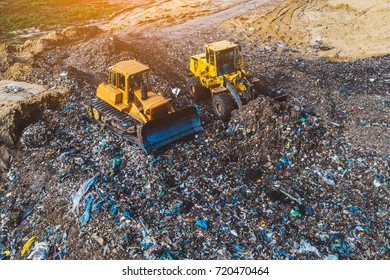 Aerial view on bulldozers working on the landfill. Environmental pollution