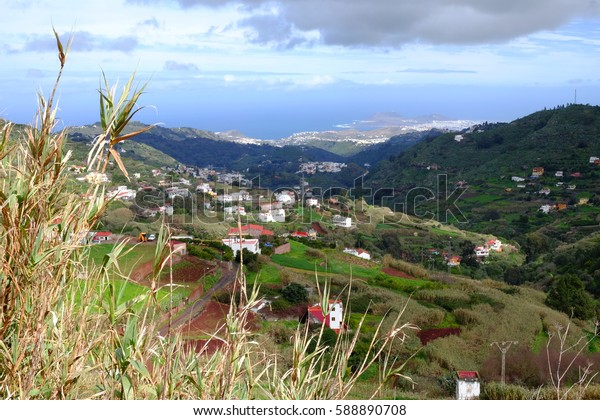 Aerial view on the central part of the Canary Island Gran Canaria with green agricultural fields, mountins, houses and the Atlantic ocean.