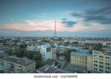 Aerial view on the city with tv tower at sunset