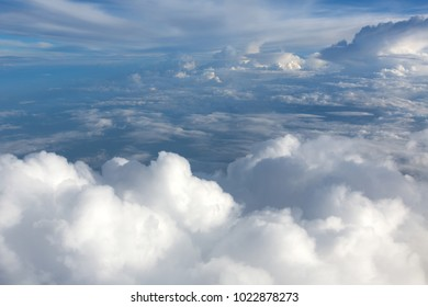 Aerial view on clouds and blue sky from airplane window