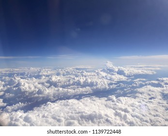 Aerial view on the clouds from the plane. Beautiful blue sky background.