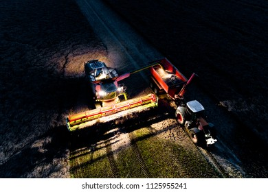 Aerial view on the combine working on the field in the night