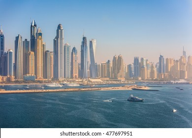 Aerial view on Dubai Marina gulf at sunset. Modern buildings and ships are seen on horizon.