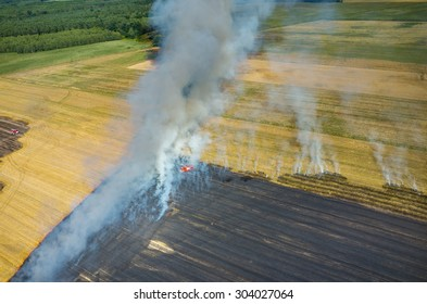 Aerial view on the fireman truck working on the field on fire