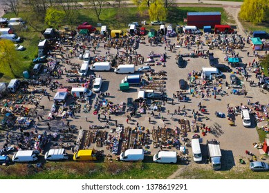 Aerial view on flea market with miscellaneous items and crowds of buyers and seller's makeshift stands.