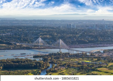 Aerial view on Fraser River and Port Mann Bridge. Taken in Greater Vancouver, British Columbia, Canada. Sunny blue sky evening.