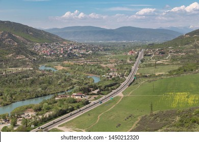 Aerial view on Georgian Military Road and Aragvi river near town of Mtskheta, ancient capital of Georgia. Blue sky with Caucasus mountains on background.