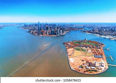 Aerial view on Governors Island and Manhattan in the foreground, New York, USA. Located in Upper New York Bay, Governors Island is home to historical fortifications Fort Jay and Castle Williams