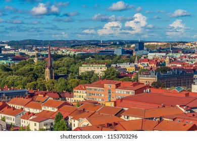 Aerial view on Haga Church (Hagakyrkan) in Göteborg, Sweden. Church surrounded by many green trees. Beautiful Gothenburg cityscape. Bright colorful rooftops of many buildings. Blue sky, white clouds.