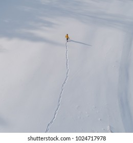 Aerial view on Man in yellow jacket walking if field covered in snow. square image