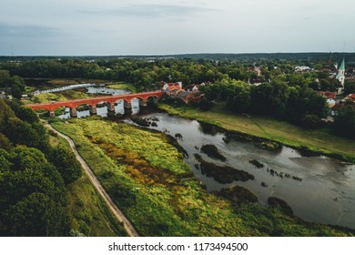 Aerial view on old red brick bridge over river Venta in Kuldiga, latvia, Small european city. Longest waterfall in europe Ventas rumba captured with drone,