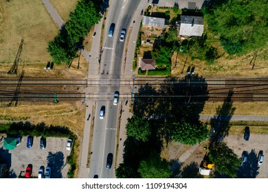 Aerial view on railroad crossing regular road from above, road junction from birds eye