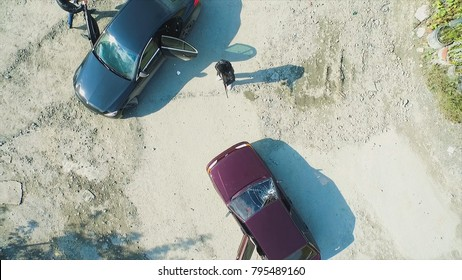 Aerial view on robbers with guns shot the car and leave. Footage. Terrorist or car thief pointing a gun at the driver. An armed man in the mask threatening pistol to the driver of the car