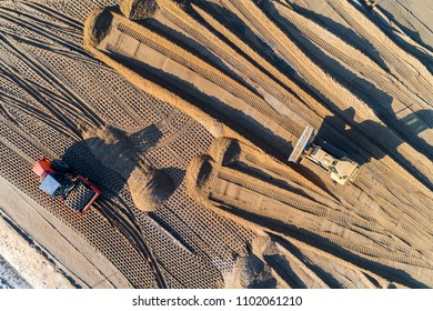 Aerial view on the roller and bulldozer working on the new modern road under construction
