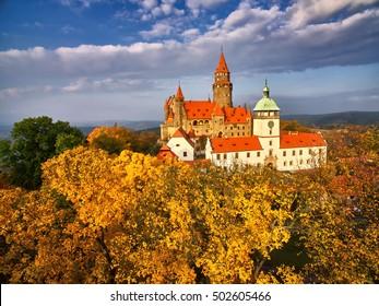 Aerial view on romantic fairy castle in picturesque autumn landscape  lit by evening sun. Castle on the hill surrounded by autumn trees. Czech landscape, Bouzov, Moravia, Czech republic.