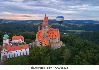 Aerial view on romantic fairytale castle Bouzov with hot air balloon next to highest tower in picturesque czech landscape. Bouzov castle, Moravia, Czech republic.