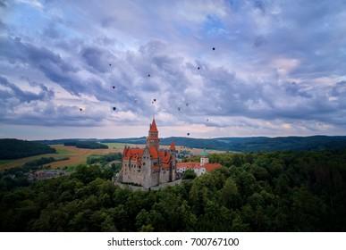 Aerial view on romantic fairytale castle Bouzov with hot air balloons against dramatic sky in picturesque czech landscape. Hot air balloon festival, Bouzov castle, Moravia, Czech republic.
