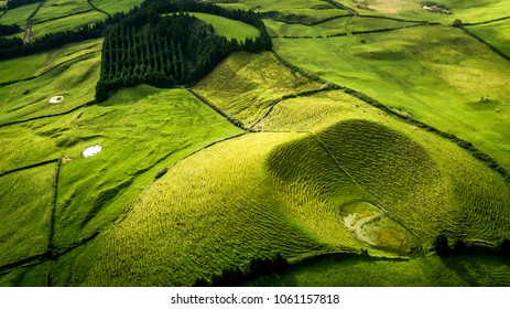 Aerial view on scenic landscape of volcano and green fields around it. Special shape of ground. Top view from drone. Azores islands, Sao Miguel, Portugal.