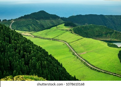 Aerial view on scenic landscape of volcanic lake Sete Cidades and green fields around it. Special shape of ground. Atlantic ocean on background. Azores islands, Sao Miguel, Portugal.