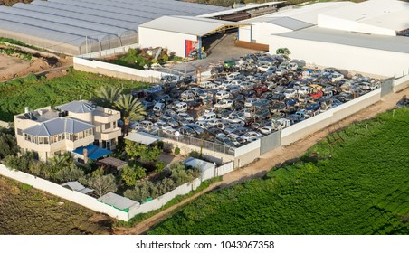 Aerial view on scrap yard with pile of crushed broken cars