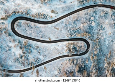 Aerial view on Serpentine in snowy winter forest. Winding road in frosty forest