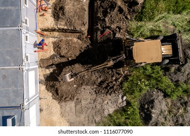 Aerial view on small excavator working on the construction site