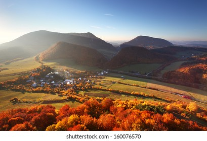 Aerial view on small town - colorful fields and trees in autumn,