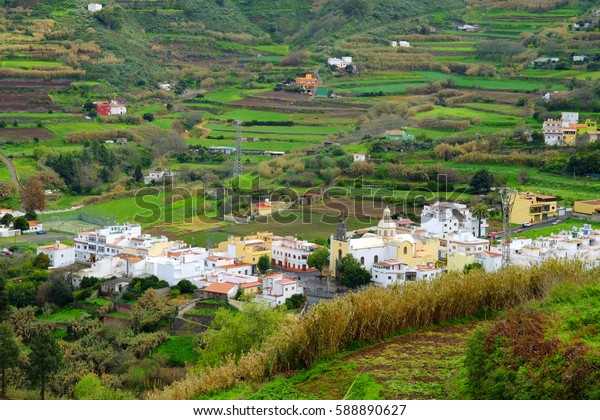 Aerial view on a small village with white houses and church and agricultural green fields around in the central part of the Canary Island Gran Canaria, Spain - 13.02.2017.