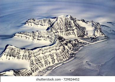 Aerial view on snow covered mountains and glaciers in Greenland / east coastal area.
