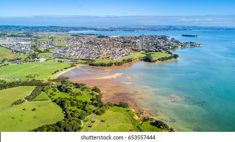 Aerial view on sunny beach with residential suburb on the background. Auckland, New Zealand.