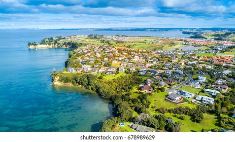 Aerial view on sunny beach with residential suburb on the background. Whangaparoa Peninsula, Auckland, New Zealand.