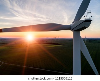 Aerial view on the sunset above the windmill on the field