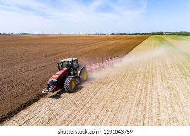 Aerial view on the tractor harrownig the large brown field