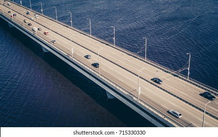 Aerial view on traffic bridge over river in sunny autumn day, cars on bridge