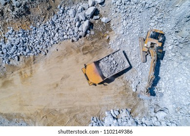 Aerial view on the truck and bulldozer working in the stone mine