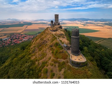 Aerial view on two stone towers  ruins of mediaeval castle Hazmburk, Hasenburg built on top of the mountain peak, surrounded by agriculture czech landscape. Aerial photography in Czech republic.