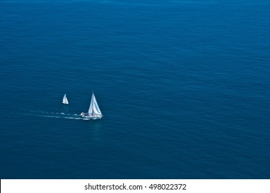 Aerial view on two white sailboats leaving wake in the blue Mediterranean sea