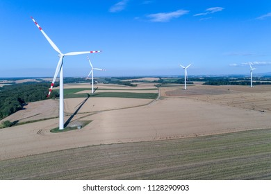 Aerial view on the windmills on the field with hay bales