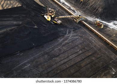 Aerial view on yellow excavator and conveyor in coal storage.
