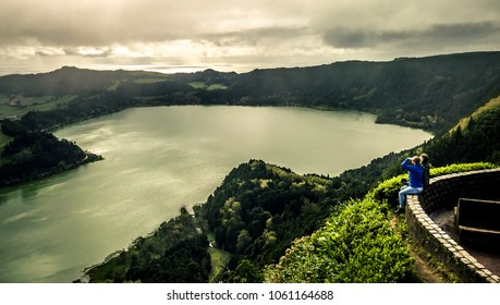 Aerial view on young couple sitting on the view point above volcanic lake Furnas and enjoying breathtaking panorama of the island Sao Miguel, Azores islands, Portugal.